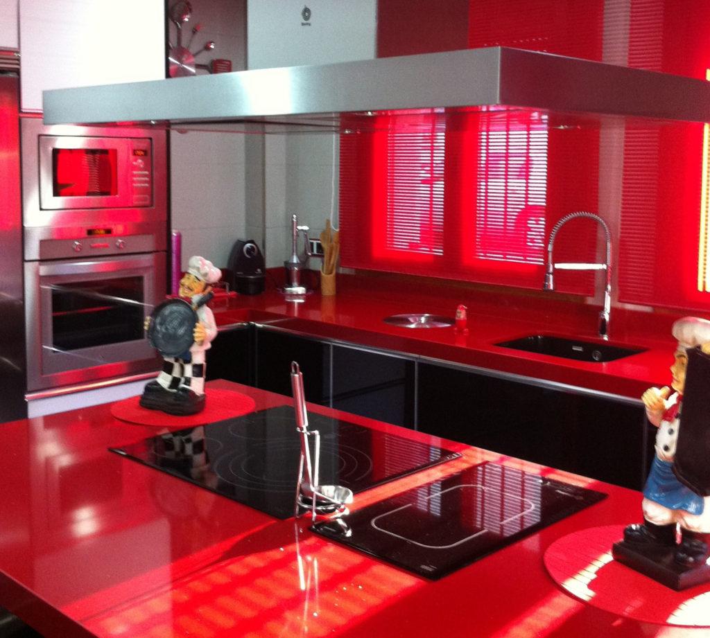 Mobiliario de cocina en cristal negro con encimera de compac rojo passion. Isla con campana y placa modular