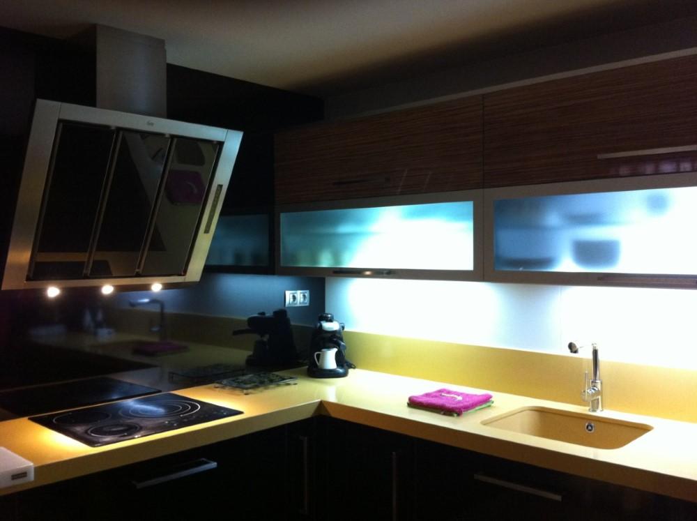 Cocina negro brillo combinada con encimera de compac y vitrinas con fondo luminoso integrado en la base del mueble. Frontal de campana en negro a juego muebles.
